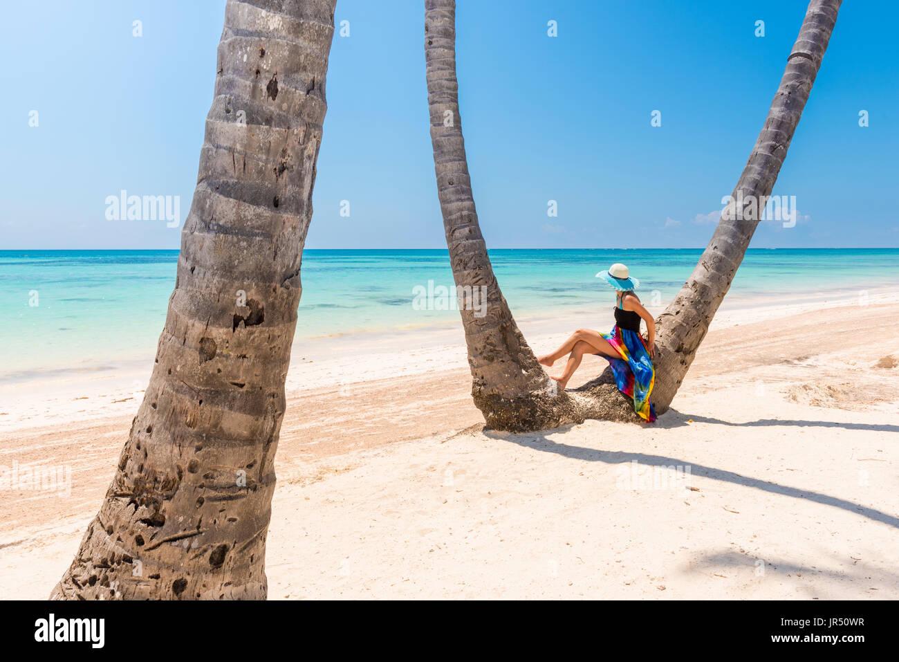 Juanillo Beach (playa Juanillo), Punta Cana, Dominikanische Republik. Frau unter hohen Palmen am Strand. Stockbild