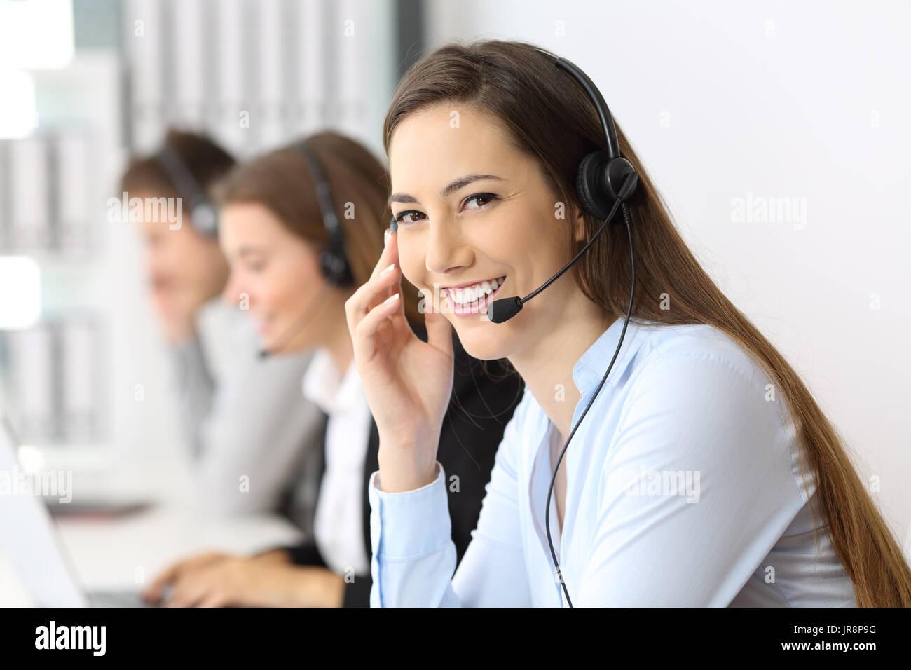 Glücklich Telemarketer betrachten Sie im Büro mit anderen Arbeitnehmern im Hintergrund Stockbild