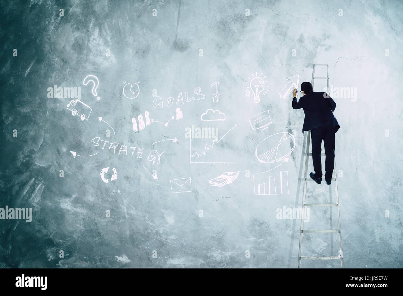 Männer Zeichnung Entwicklung Grafik Strategie auf die graue Wand. Stockbild
