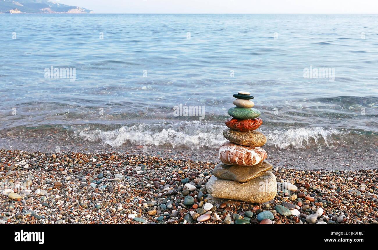 Steinen Gleichgewicht am Strand bei Sonnenuntergang. Konzept des Friedens und der Harmonie. Stockbild
