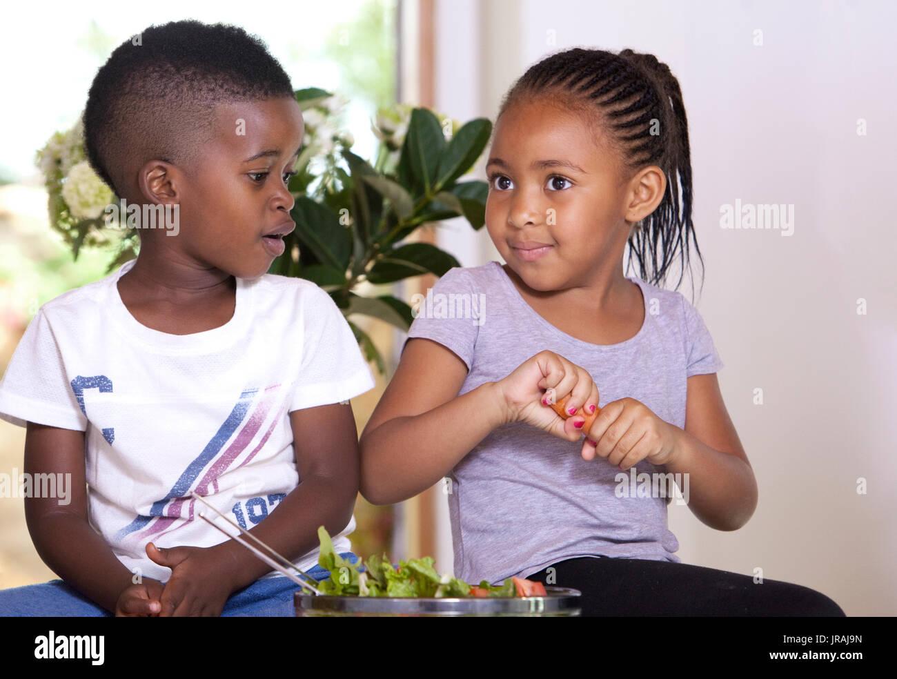 Kleines Mädchen brechen eine Karotte mit ihrem Bruder zu teilen Stockfoto