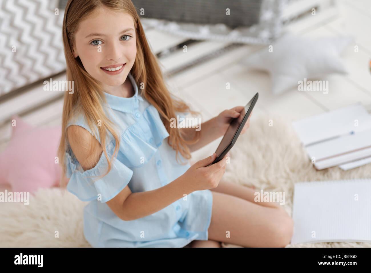 Adorable girl mit digitalen Tablet grinste breit für Kamera Stockbild
