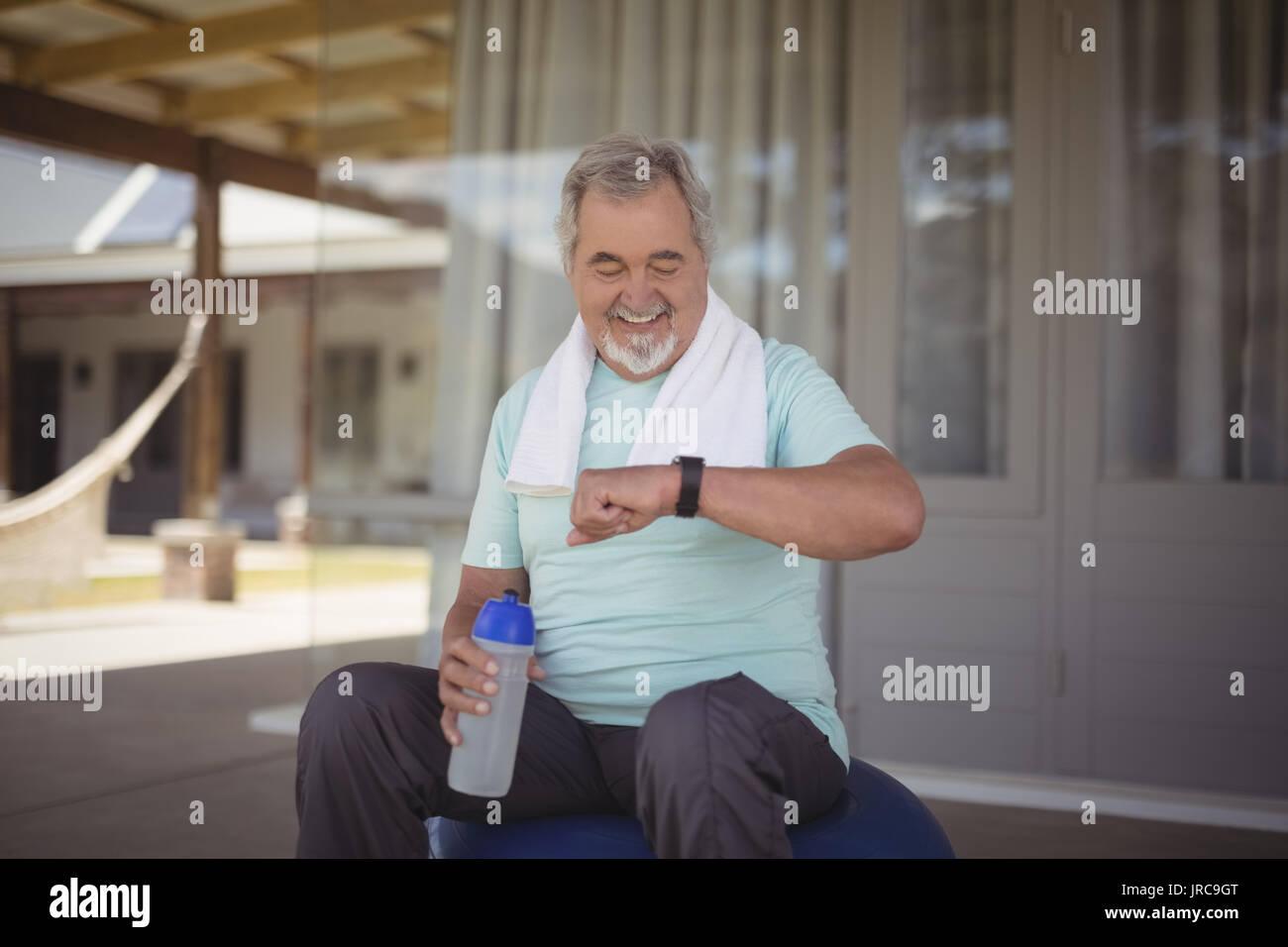 Ältere Menschen gleichzeitig auf der Armbanduhr nach Arbeiten an der Veranda Stockbild