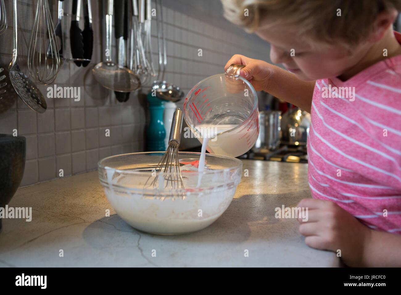 Junge gießen Milch in den Teig an küchenutensil Stockbild