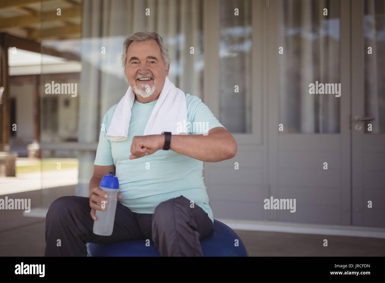 Lächelnd älterer Mann gleichzeitig auf armbanduhr nach Arbeiten an der Veranda Stockbild