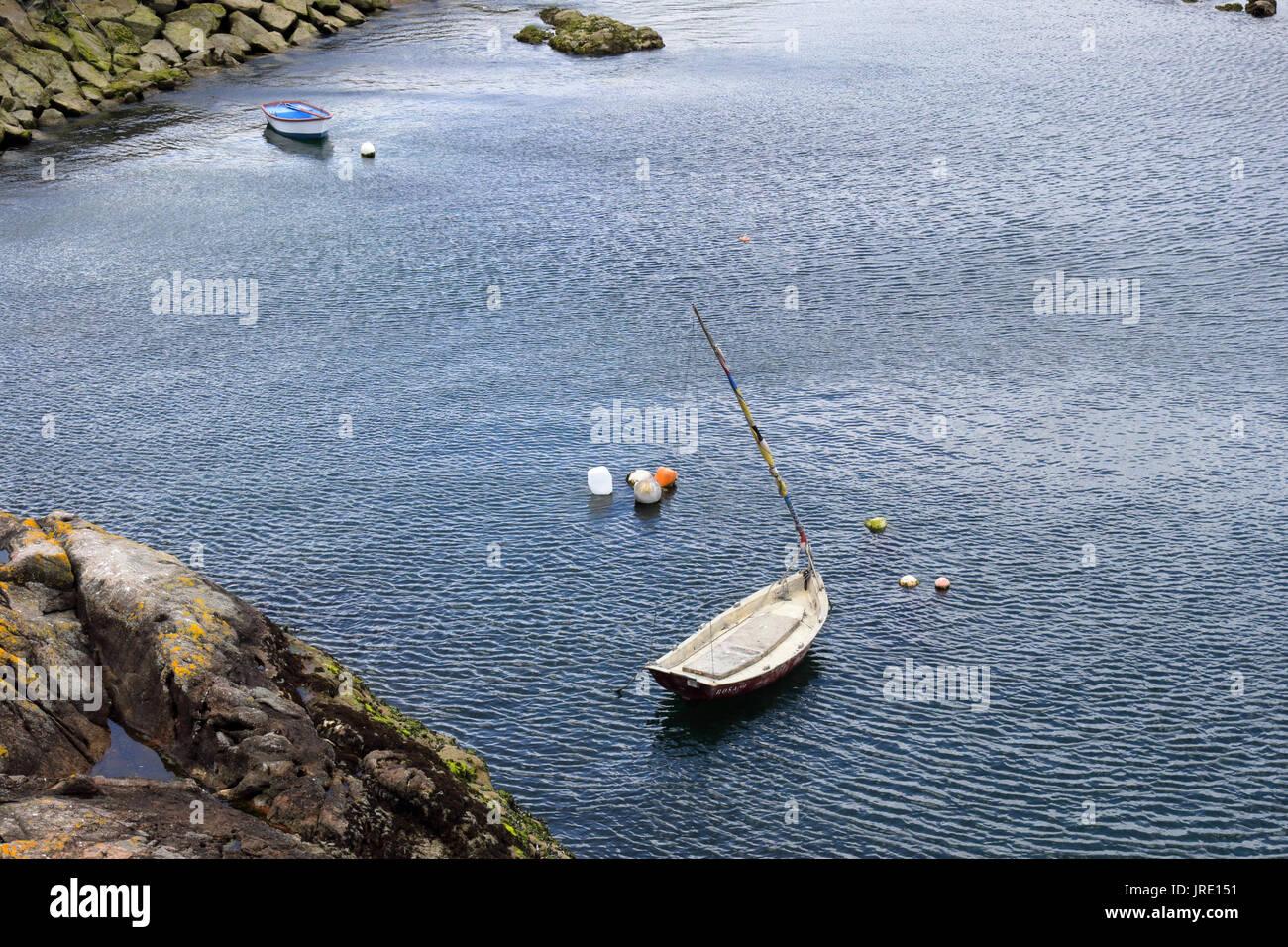 Zwei kleine weiße Boote aus Holz in einem Hafen neben einem Felsen Pier und Klippen mit einige Bojen verankert. Stockbild