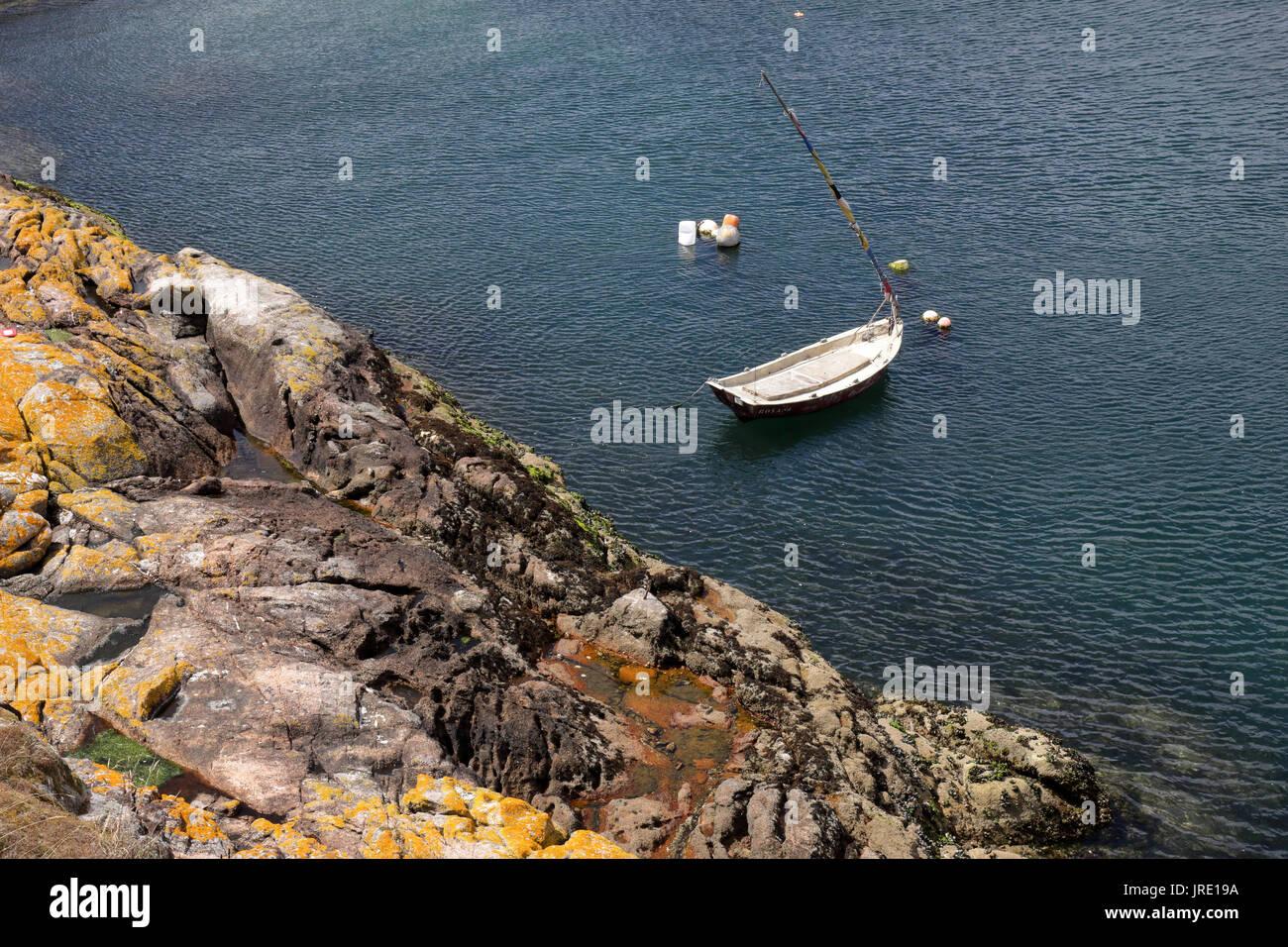 Eine kleine weiße hölzernes Boot in einem Hafen vor Anker neben einem Felsen Pier und Klippen mit einige Bojen. Stockbild