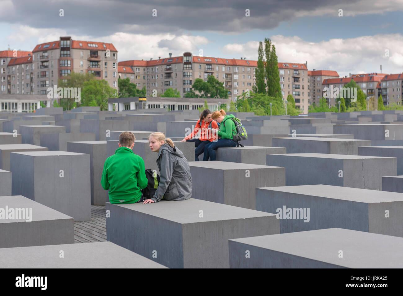 Berlin Holocaust Memorial, eine Gruppe von jungen Studenten bei einem Besuch des Holocaust-Mahnmals in Berlin, Deutschland miteinander chatten Stockbild