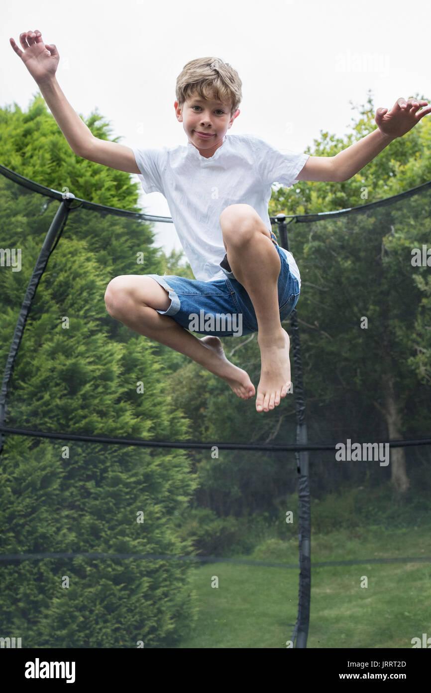 Mid Air Shot von Jungen auf Trampolin im Garten Stockbild