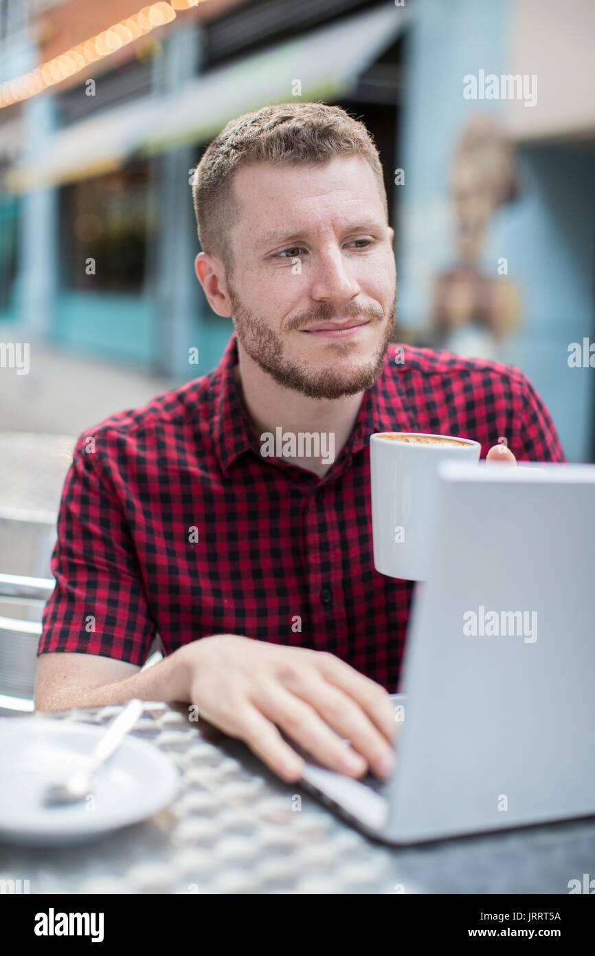 Junge Mann an Café im Freien Arbeiten am Laptop Stockbild