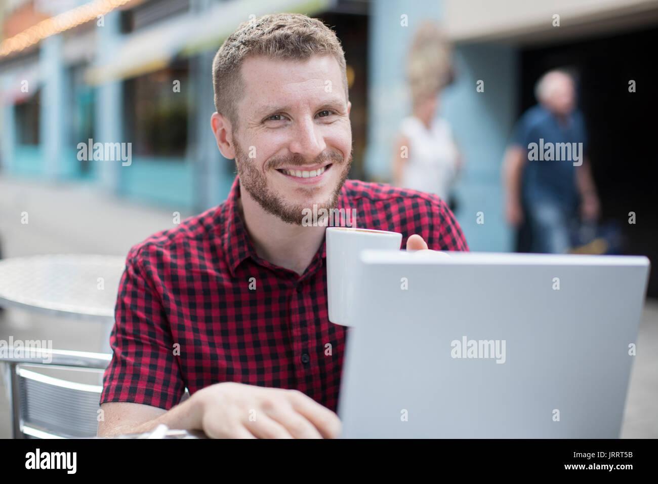 Porträt des jungen Mannes im Outdoor-Cafe auf Laptop Stockbild