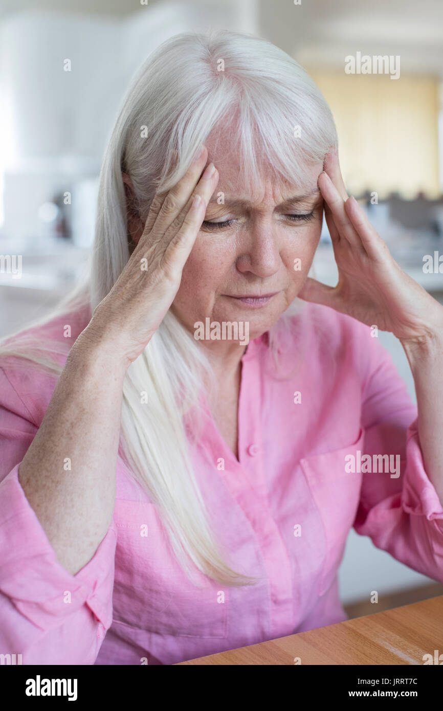 Reife Frau zu Hause leiden unter Kopfschmerzen. Stockbild