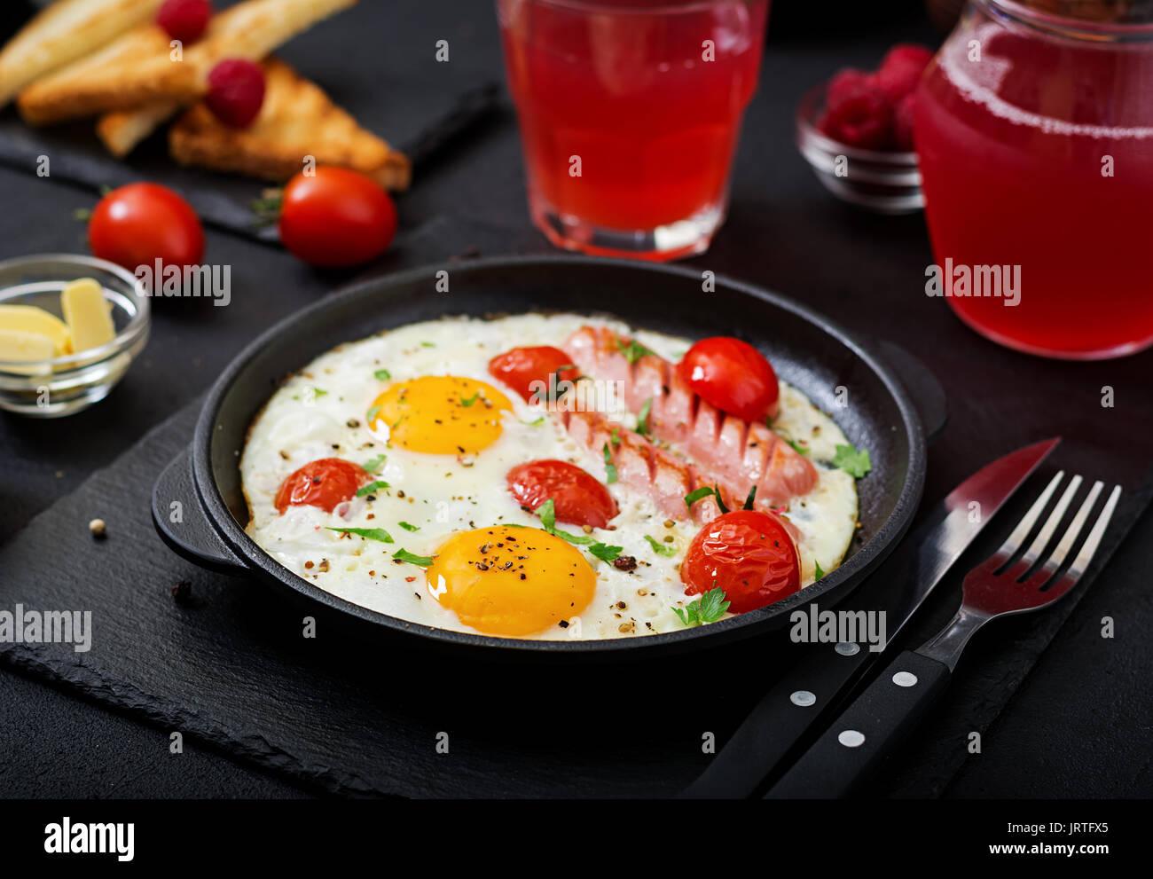 Englisches Frühstück - Spiegelei, Tomaten und Würstchen. Stockbild