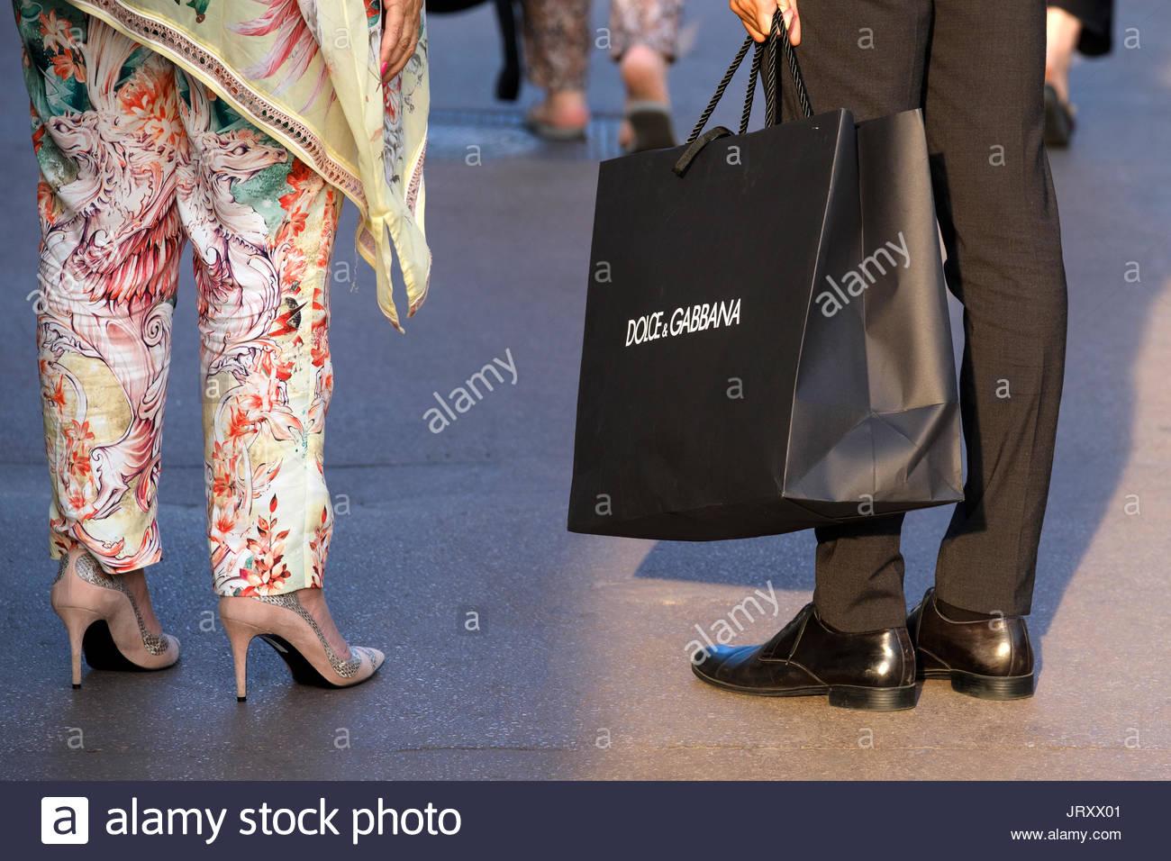 Eine persönliche Assistentin für den Dolci & Gabbana stoe in Cannes, Frankreich tragen der Einkaufstasche der Käufe von einem reichen Client gemacht, als sie Blätter Stockbild