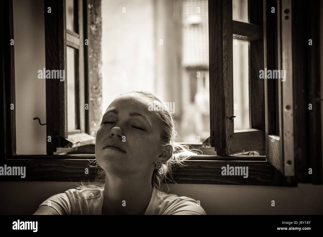 Nachdenkliche junge Frau mit geschlossenen Augen in Gedanken entspannen und träumen in der Nähe der geöffneten Fenster in Schwarz und Weiß im traditionellen Stil mit Dramati verloren Stockbild