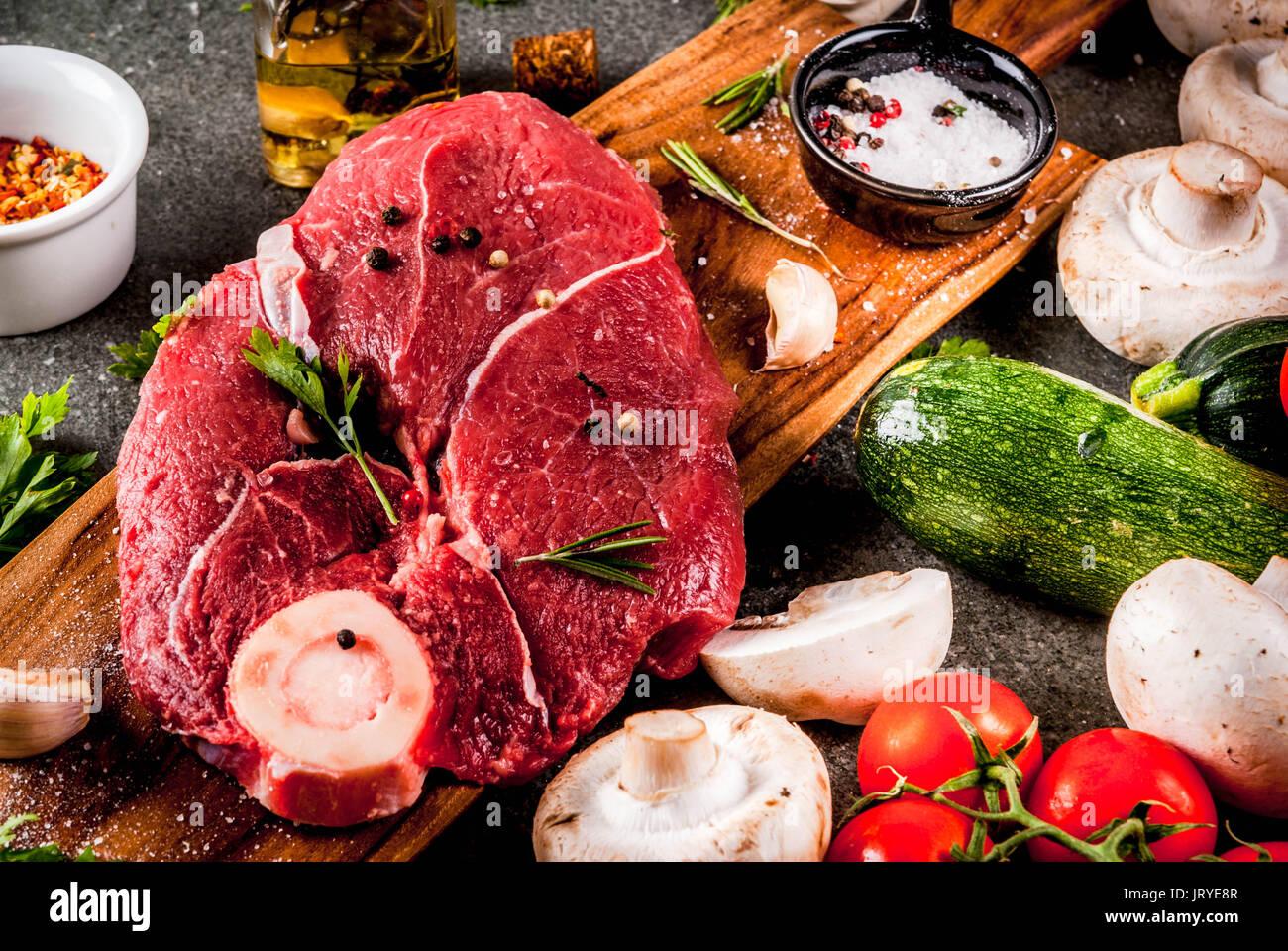 Rohes Fleisch mit Zutaten für das Abendessen. Rinderfilet, Filet, auf ein Schneidbrett, mit Salz, Pfeffer, Petersilie, Rosmarin, Öl, Knoblauch, Tomaten, Pilze, Stockbild