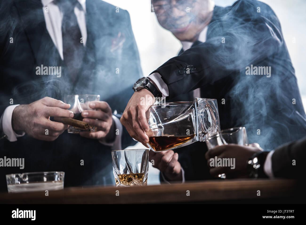 7/8-Ansicht von Business Team Zeit, rauchen Zigarren und trinken Whiskey Stockbild