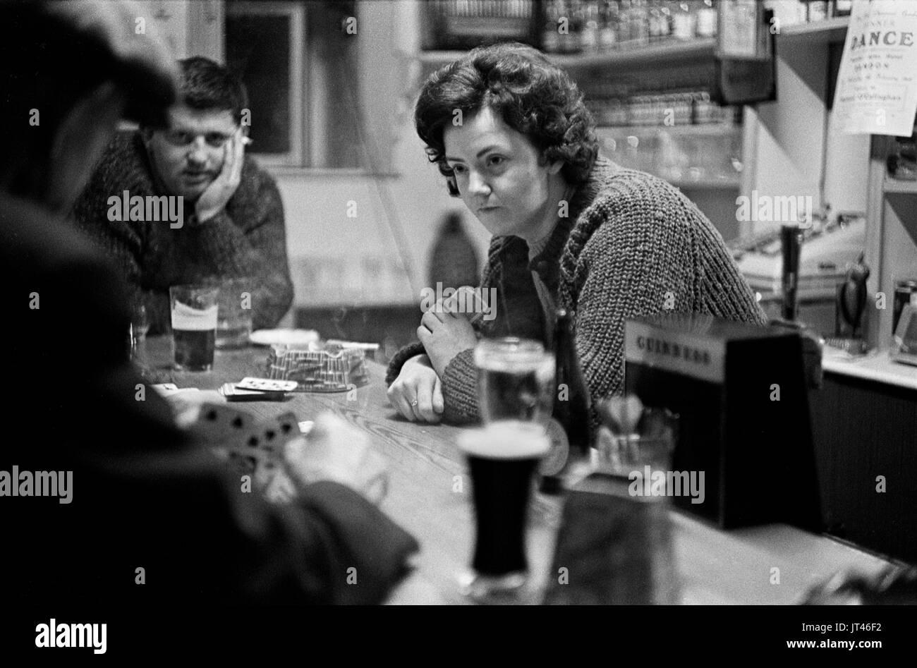 Irland West Küste Gruppe Menschen spielen Karten in der Dorfkneipe, Wirtin Spielkarten mit Kunden Freundschaft Gemeinschaft Alltag 1969 1960s HOMER SYKES Stockbild