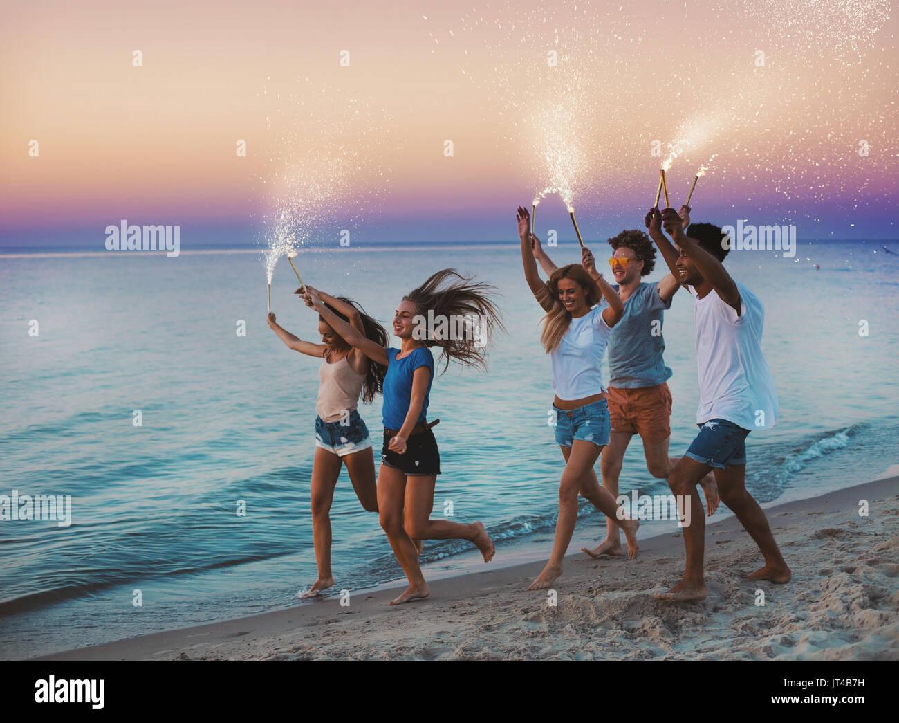 Glücklich lächelnde Freunde laufen am Strand mit funkelnden Kerzen Stockbild