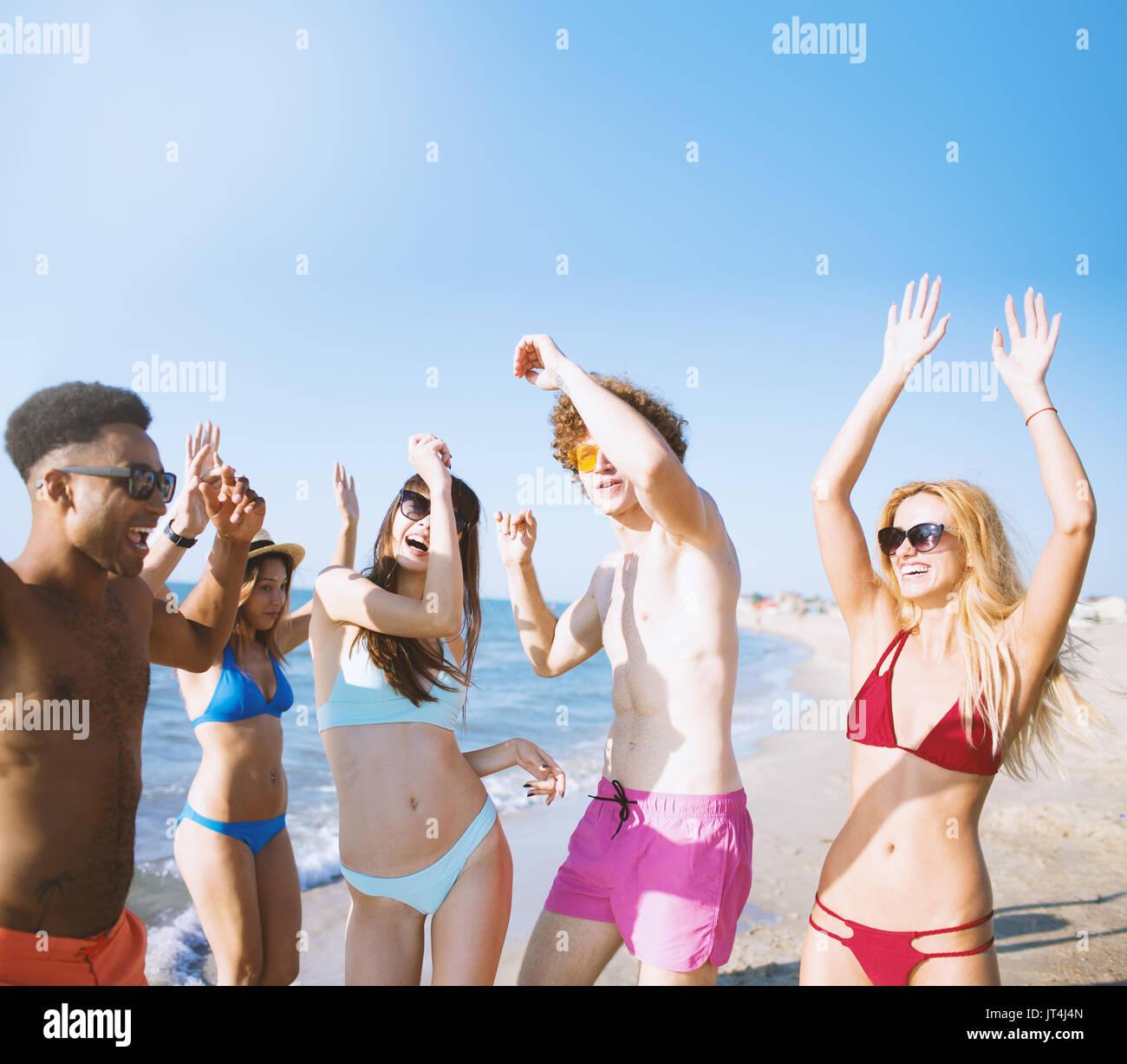 Freunde tanzen am Strand Stockbild