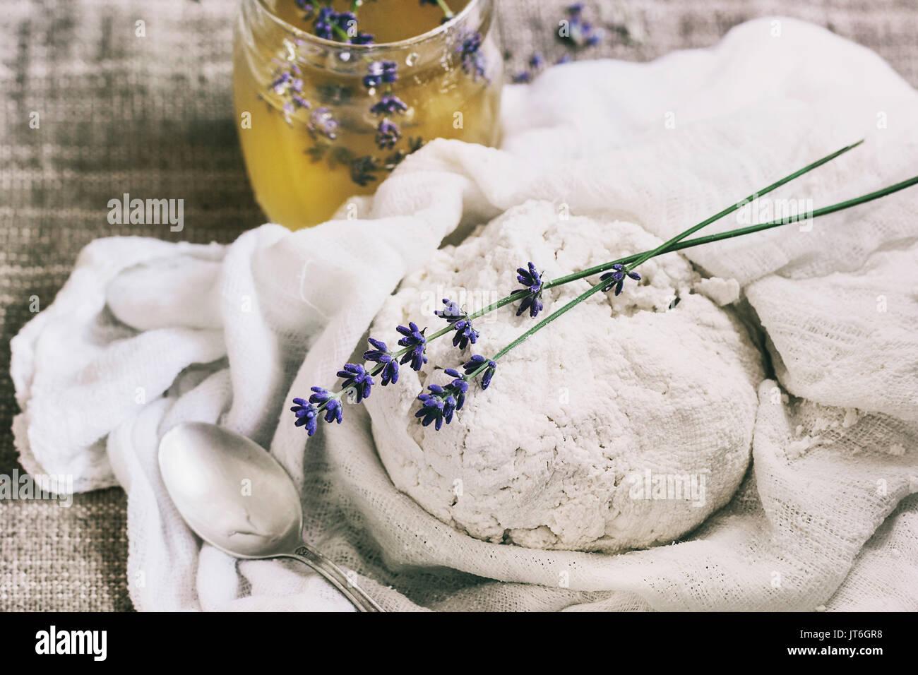 Frische Küche hausgemachte Hüttenkäse in Gaze Textil mit Lavendelblüten und Honig über Sack Hintergrund. Rustikaler Stil, Tageslicht Stockbild