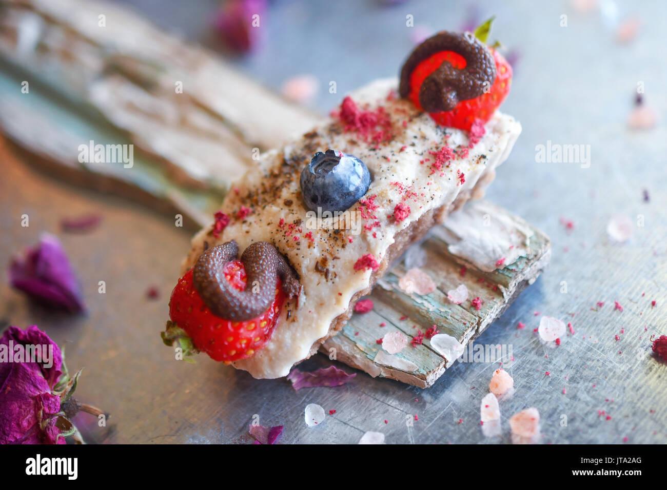 Veganer Käsekuchen Bissen mit Cashew Creme, mit Schokolade überzogene Erdbeeren und Heidelbeeren, Finger sortierte Snack. Stockbild