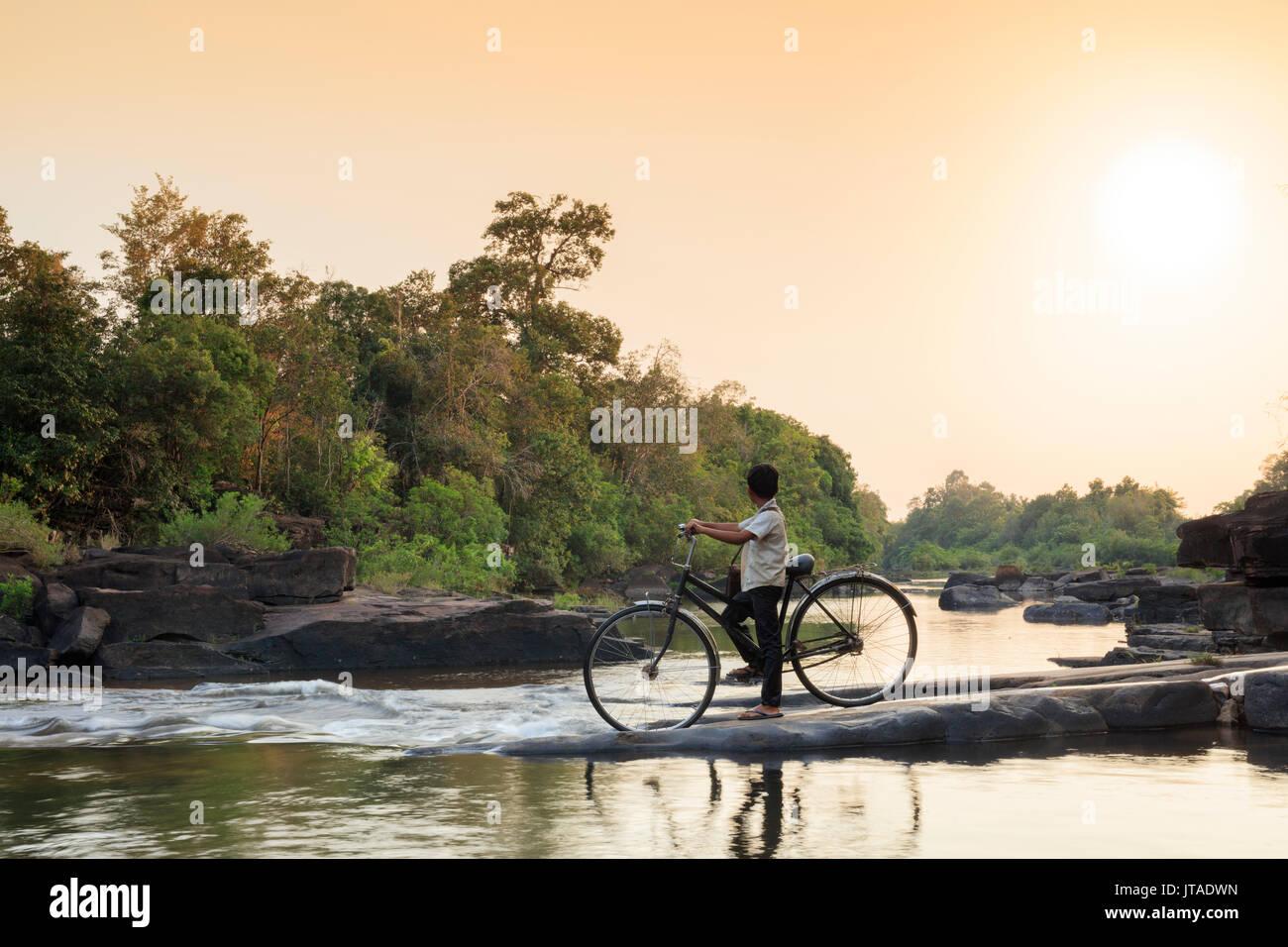 Schule Jungen auf einem Fahrrad, die einen Fluß überquert, auf dem Weg zur Schule, Chi Phat, Koh Kong, Kambodscha, Indochina, Südostasien, Asien Stockbild