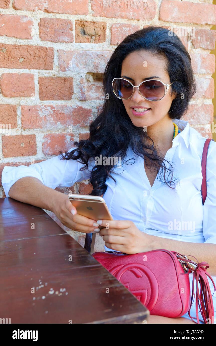 Junge Brasilianer (Lateinamerika) (Latina) Frau, 20 bis 29 Jahre alt mit Ihrem Handy in einem Cafe, Rio de Janeiro, Brasilien Stockfoto