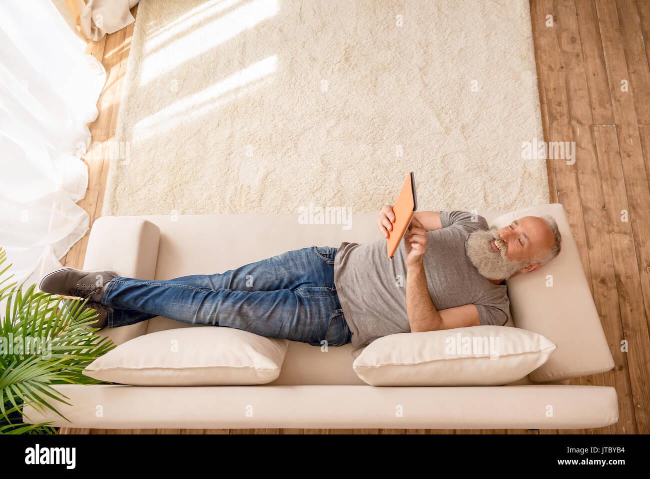 Älterer bärtiger Mann lächelnd und mit digitalen Tablet und liegend auf dem Sofa zu Hause Stockbild