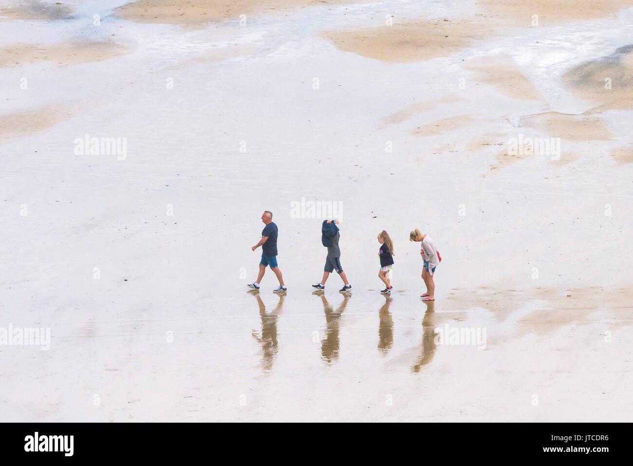 Eine Familie der Urlauber wandern in einzelne Datei auf einem Strand in Newquay, Cornwall. Stockbild