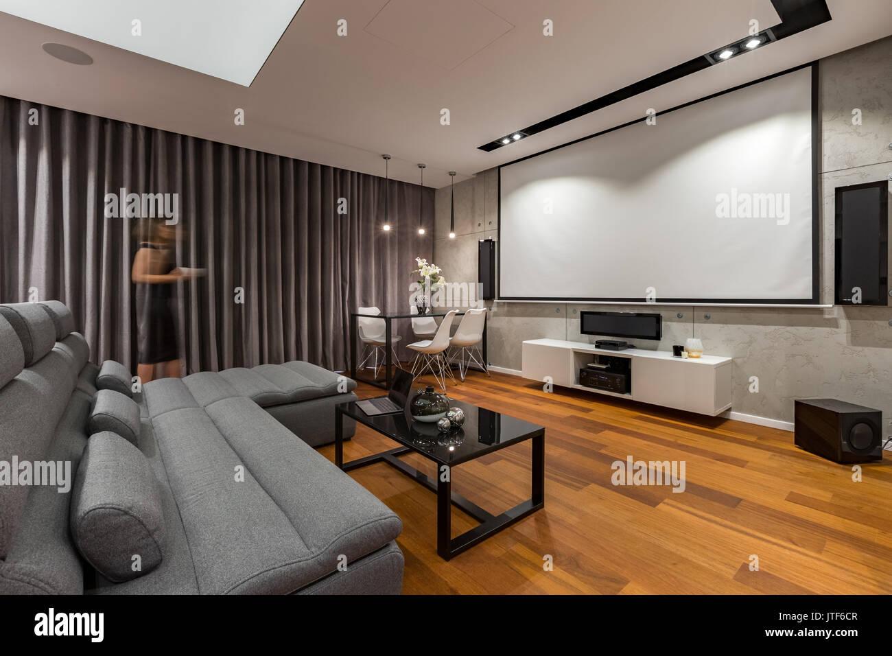 Wohnzimmer mit Leinwand, grau Couch und Couchtisch schwarz ...