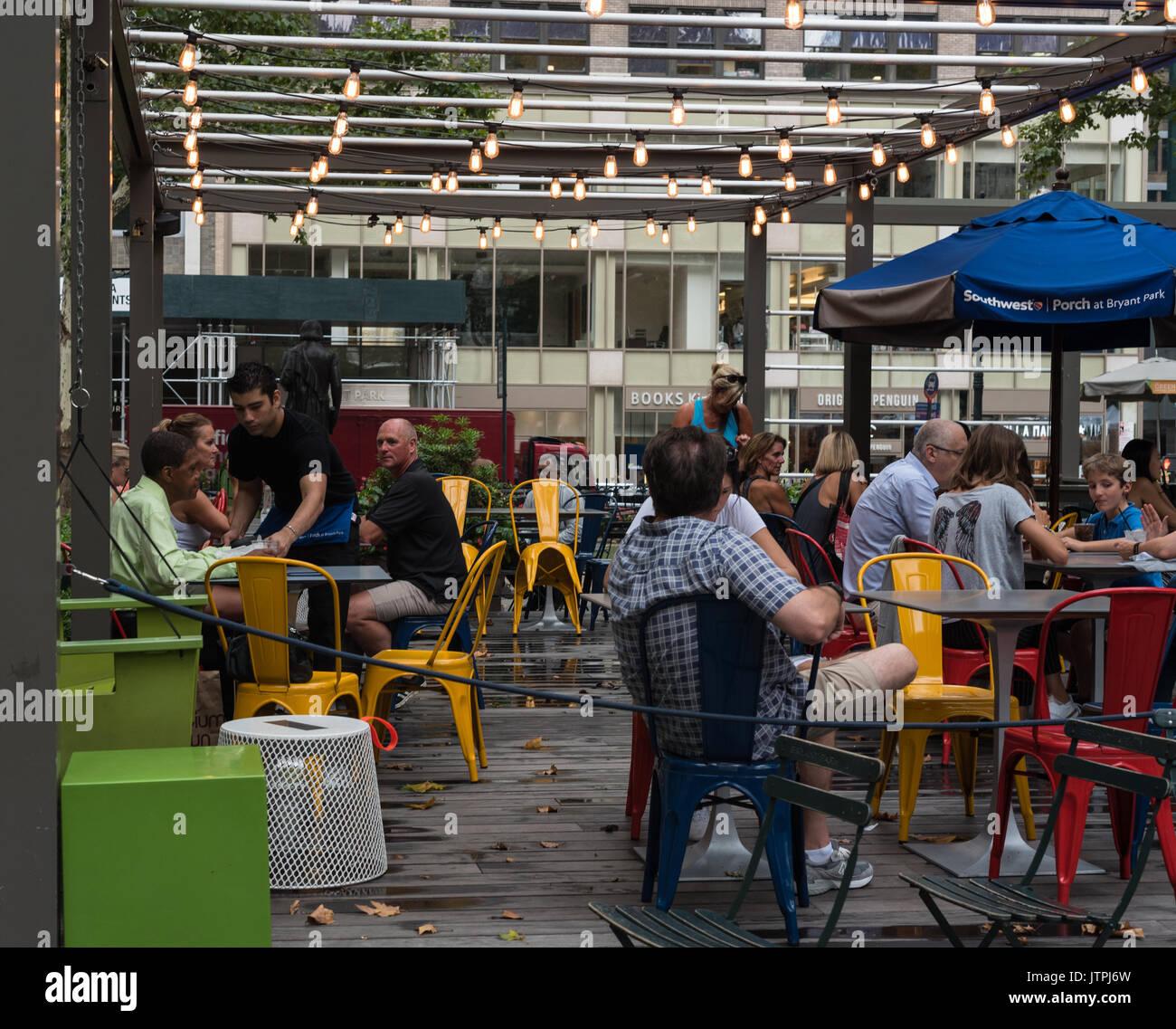 Freunde und Familien für Snacks und Gespräch an einer im Cafe im Bryant Park, New York City. Redaktionelle Verwendung. Stockbild