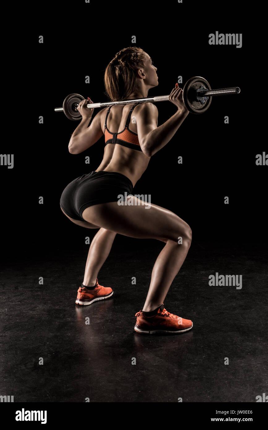 Muskulöse junge Frau in Sportbekleidung heben Barbell und Wegsehen Stockbild
