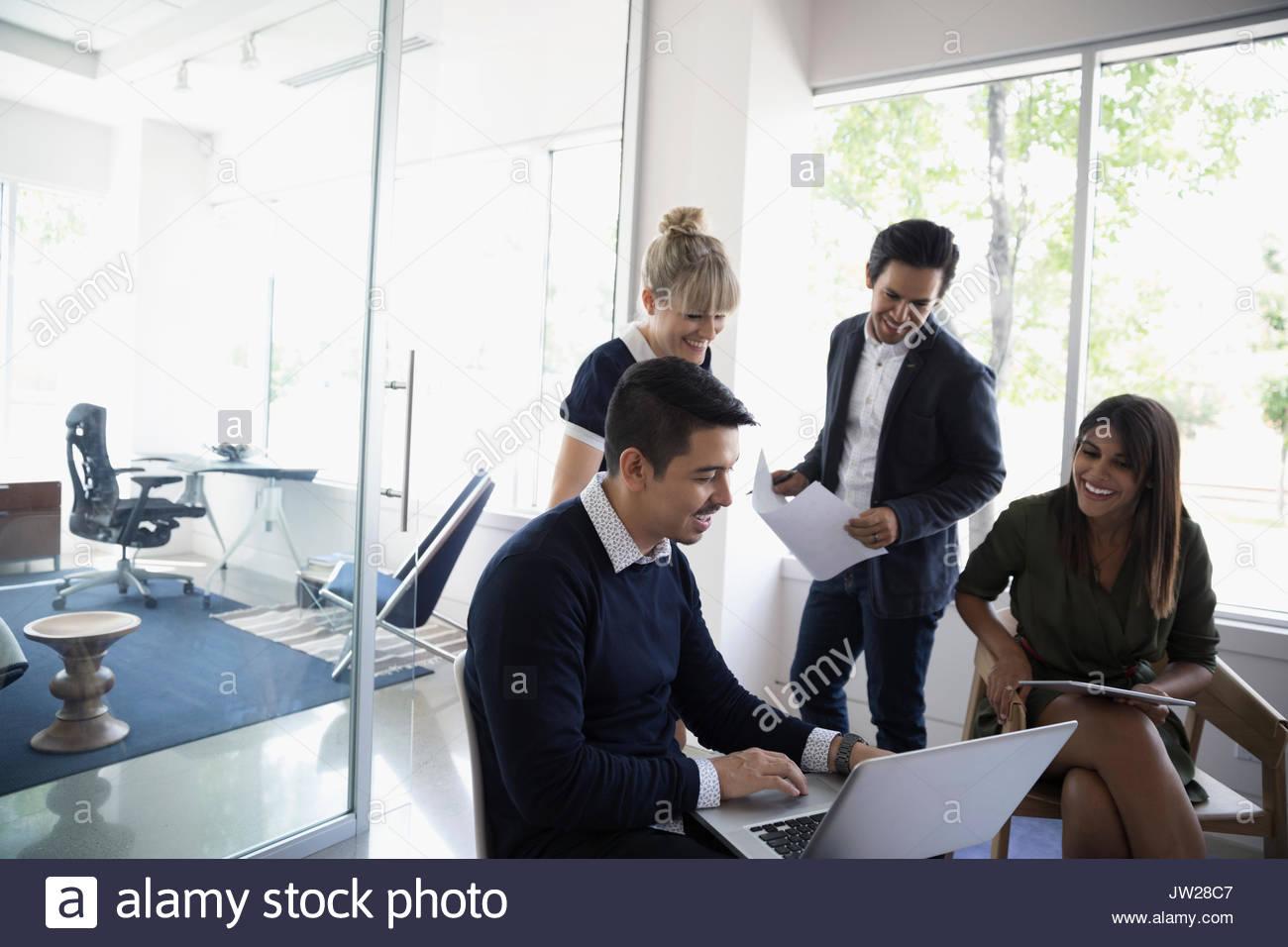 Geschäftsleute, die mit Laptop im Büro treffen Stockbild