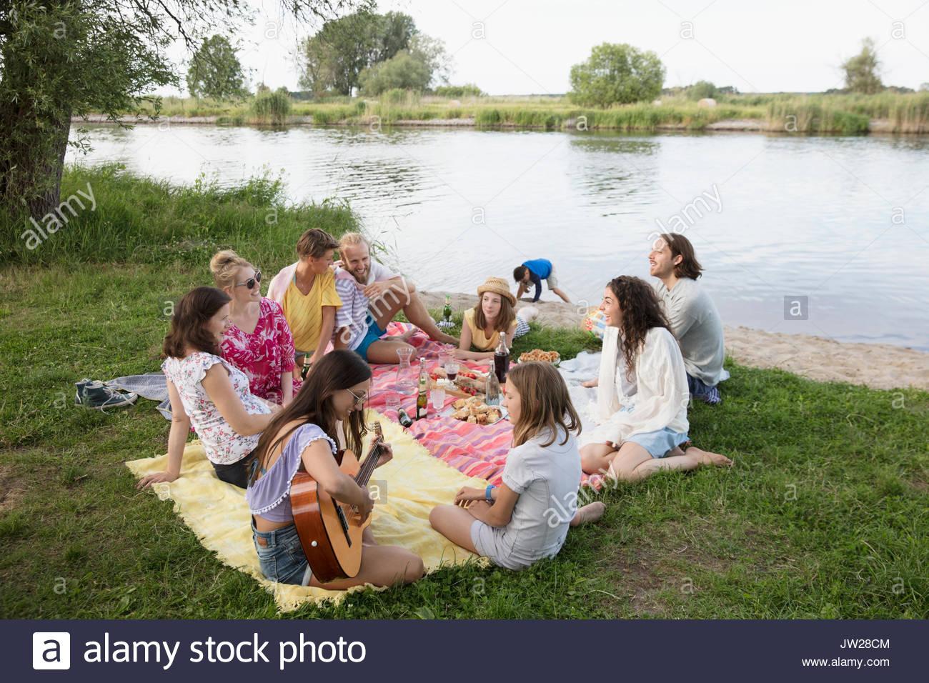 Freunde und Familie entspannen, genießen Sommer Picknick am See Stockbild