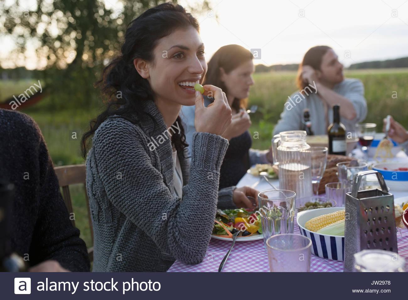 Lächelnde Frau essen Garden Party Abendessen Stockbild