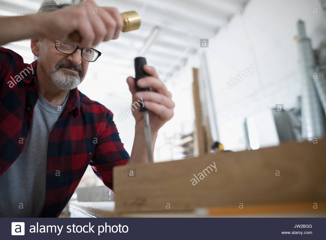 Männliche Tischler Gewindebohren Meißel auf Holz Block an der Werkbank in Werkstatt Stockbild