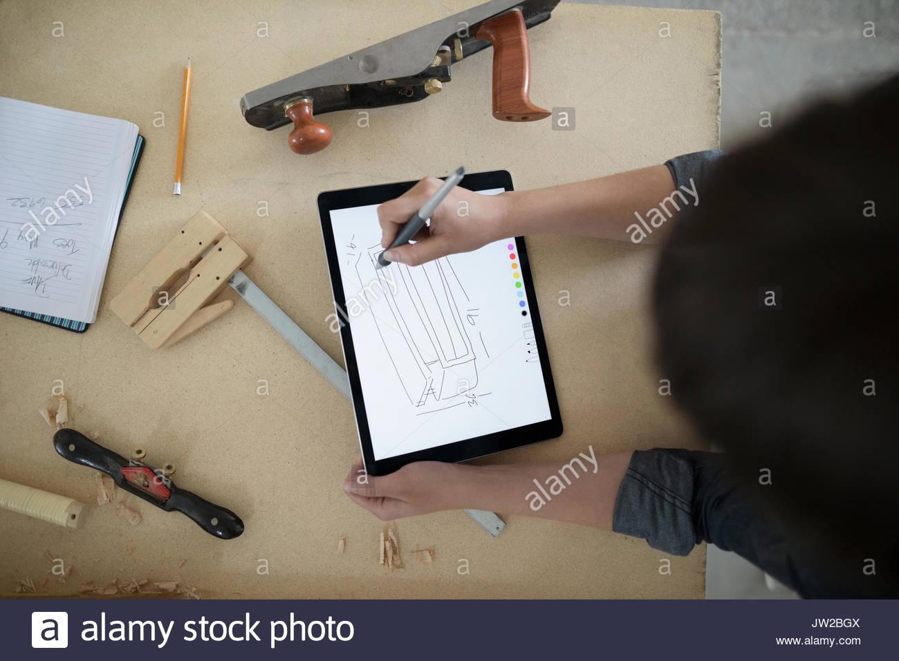 Ansicht von oben Frau Carpenter skizzieren mit digitalen tablet Stift an der Werkbank in Werkstatt Stockbild