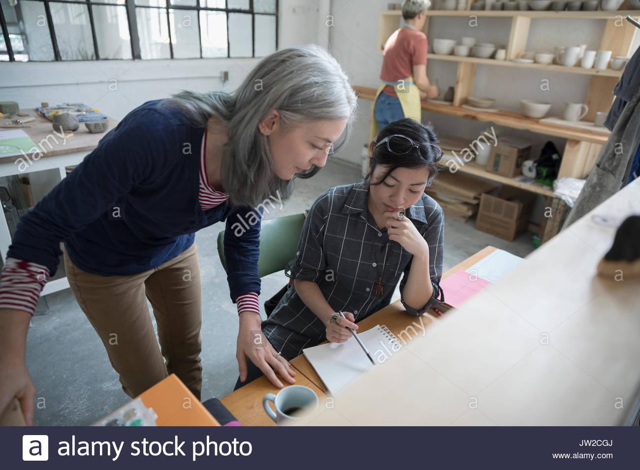 Künstlerinnen skizzieren am Schreibtisch in art studio Stockbild