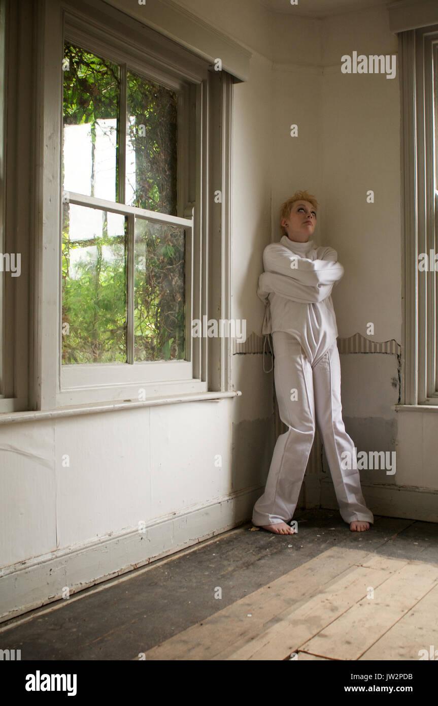Mädchen in einer Zwangsjacke in einem verlassenen Haus Stockbild
