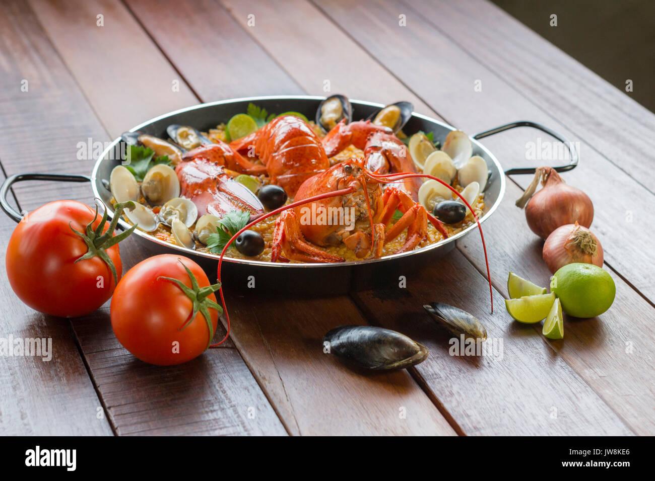 Gourmet Meeresfrüchte Valencia Paella mit frischen Scampi, Muscheln, Muscheln und Tintenfisch auf herzhafte Safran Reis mit Erbsen und Zitronenscheiben, Ansicht schließen Stockbild