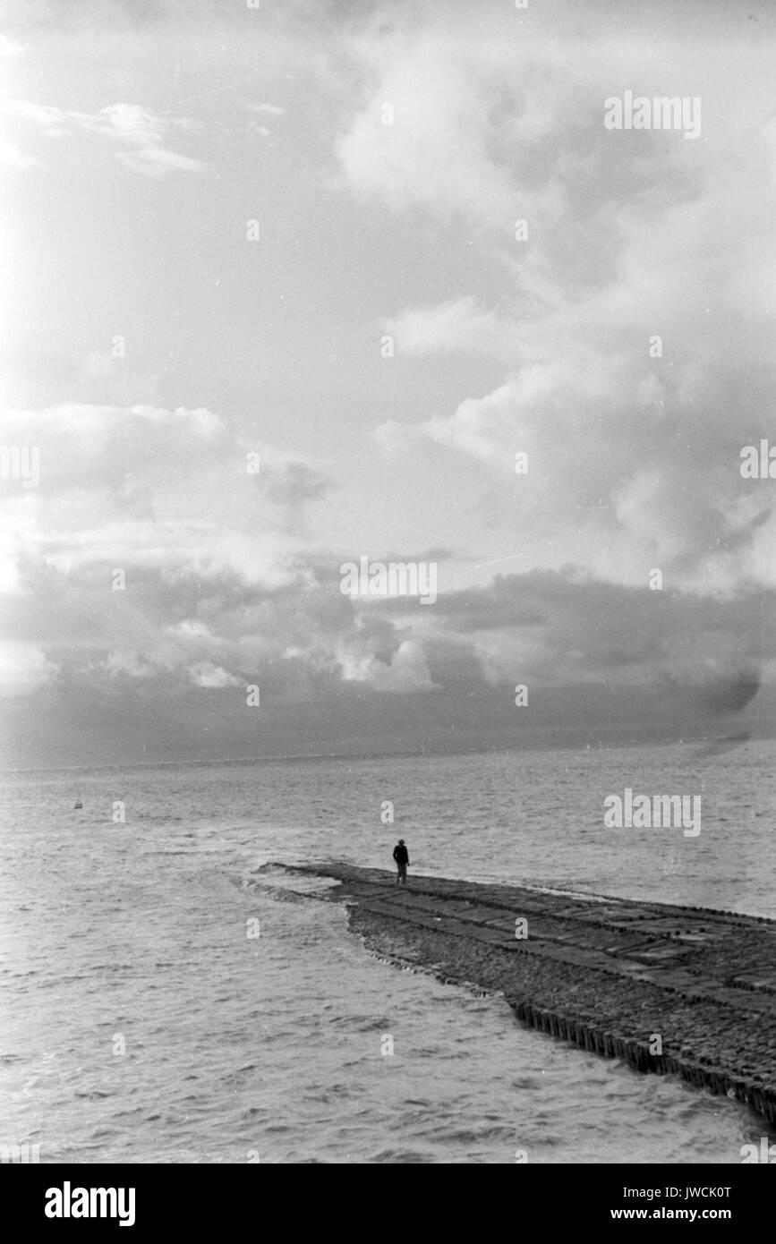 Long Shot von Mensch zu Fuß entlang der Mole am Meer. Stockbild