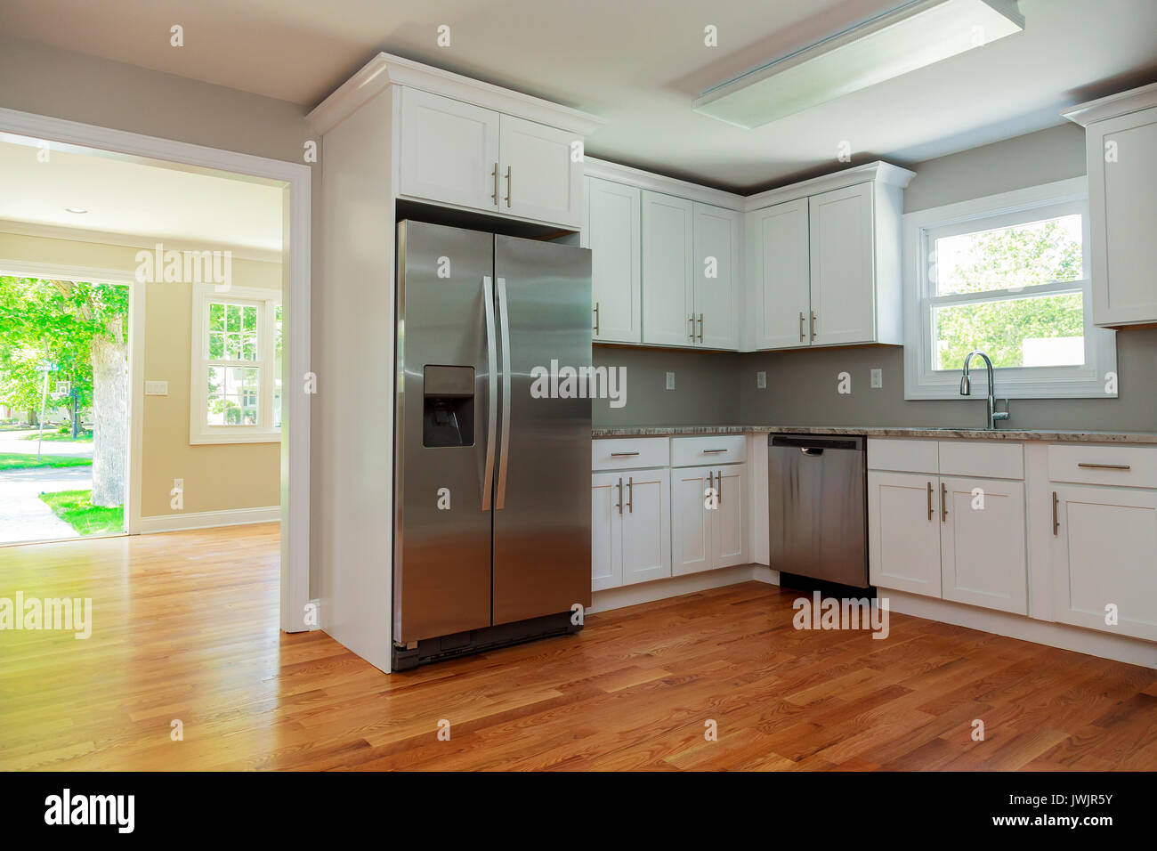 Weiße Küche mit Spüle, Schränke, und Massivholzböden in neuen Luxus ...