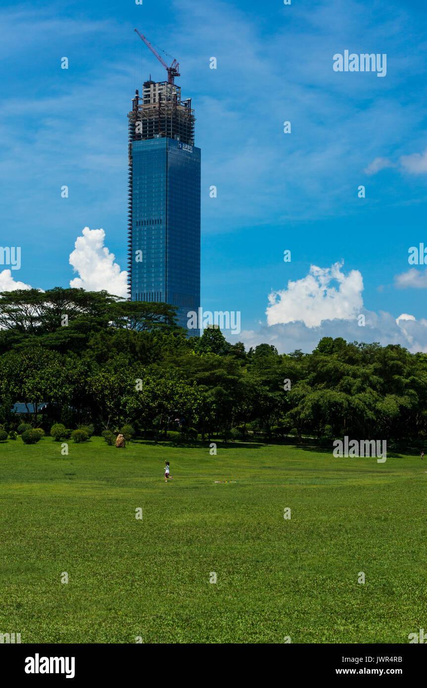 Unvollendete Office Tower in Shenzhen, China, mit Blick auf einen Park als Junge Kind versucht, einen Drachen zu fliegen Stockbild