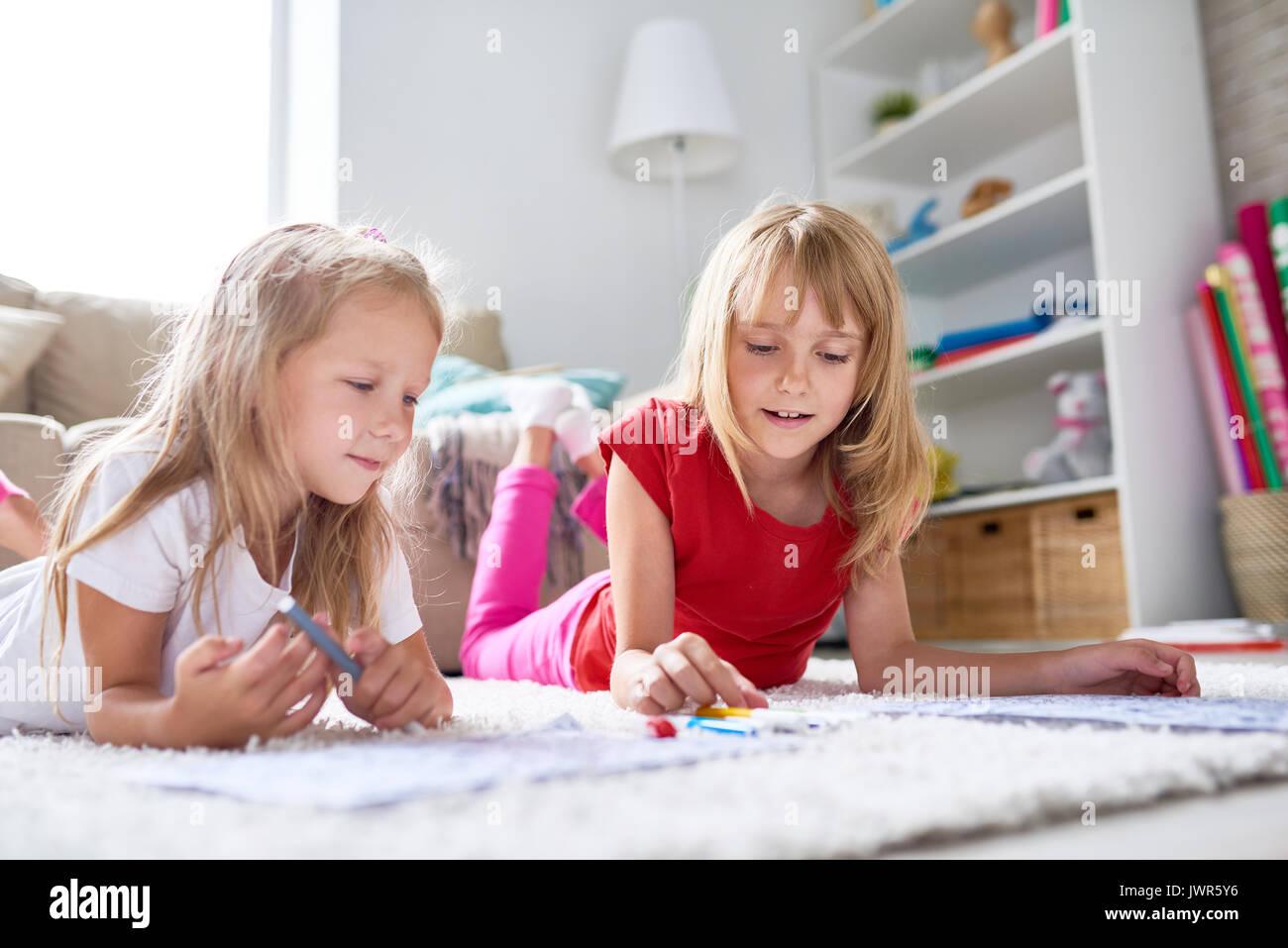 Kreative kleine Mädchen liegen auf Teppich und Zeichnen von Bildern ...