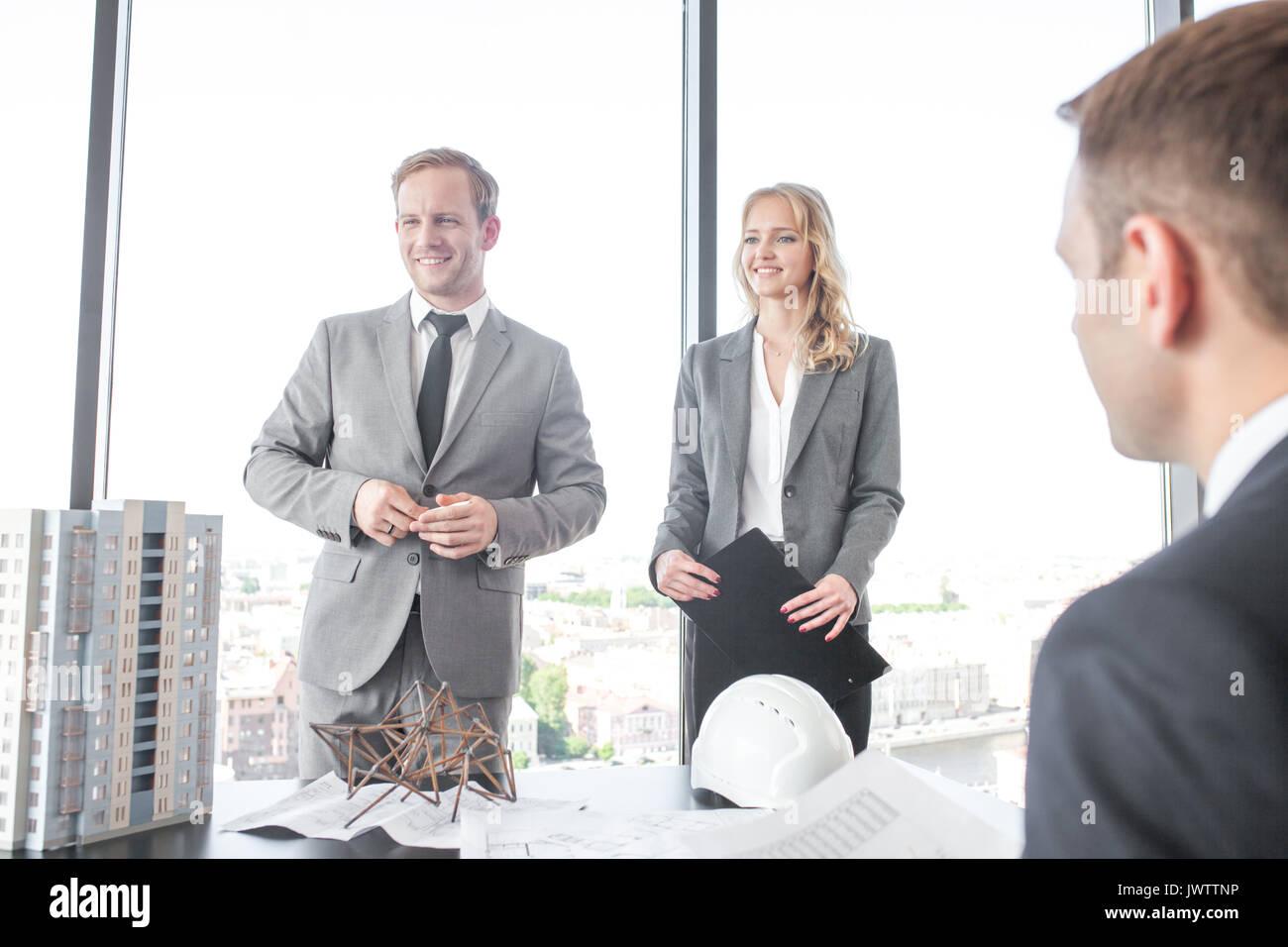 Business Präsentation von Architekten für Investoren, die Diskussion über neue Bau formen, Modell für modernes, mehrstöckiges Wohnhaus Haus, bluepr Stockbild