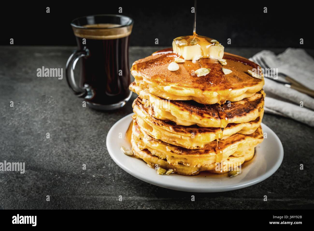 Herbstliche traditionelles Essen. Stapel von Kürbis Pfannkuchen mit Butter, Kürbiskerne und Ahornsirup. Mit einer Tasse Kaffee. Auf einem schwarzen Steintisch. Kopieren Sie sp Stockfoto
