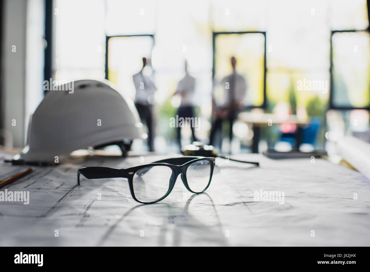 Verschiedene Architektur liefert am Arbeitsplatz mit Architekten hinter, auf Vordergrund konzentrieren Stockbild