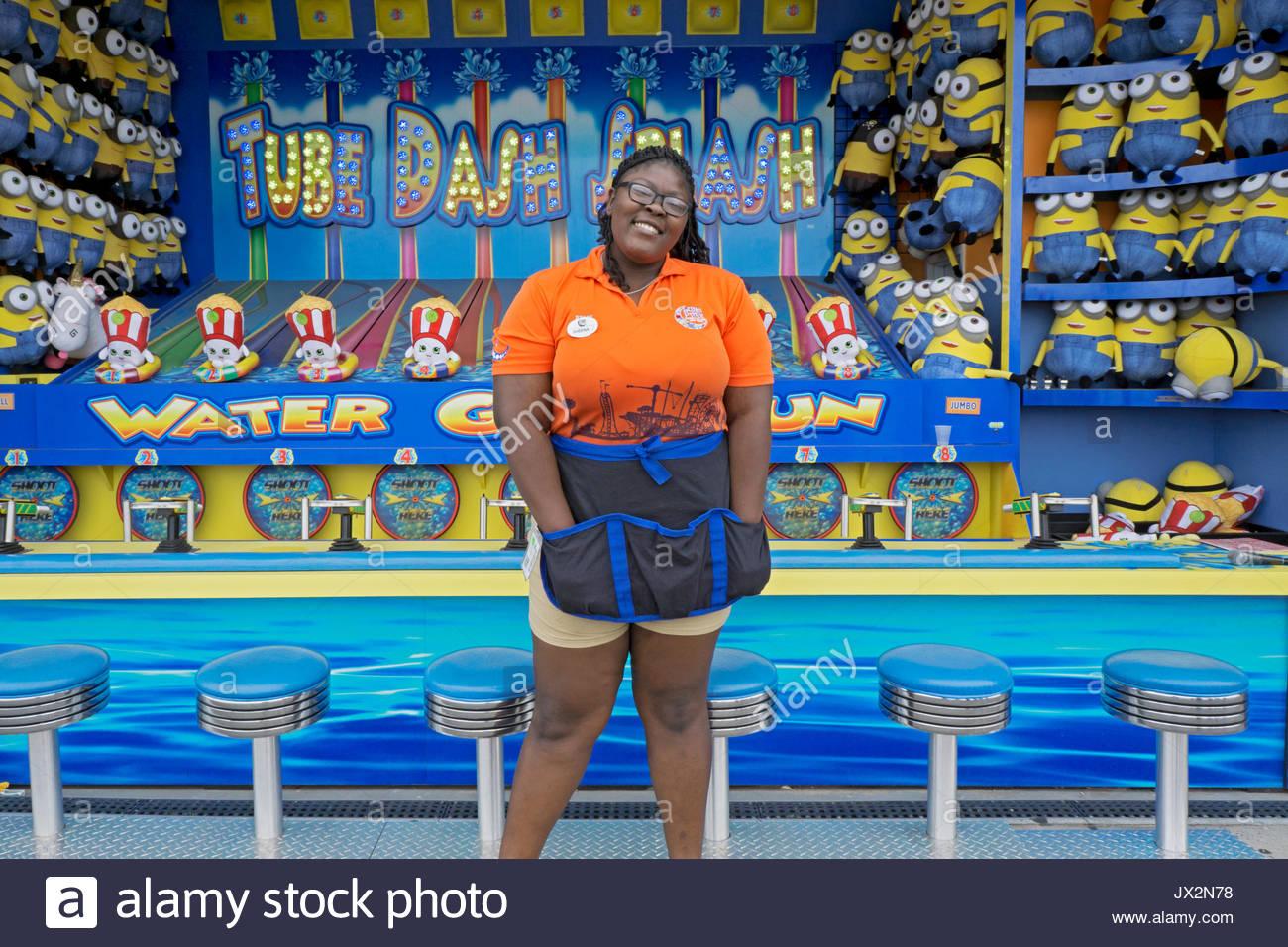 Ein College Mädchen an ihrem Ferienjob in einem Arcade Spiel auf dem Boardwalk Coney Island in Brooklyn, New York. Stockbild