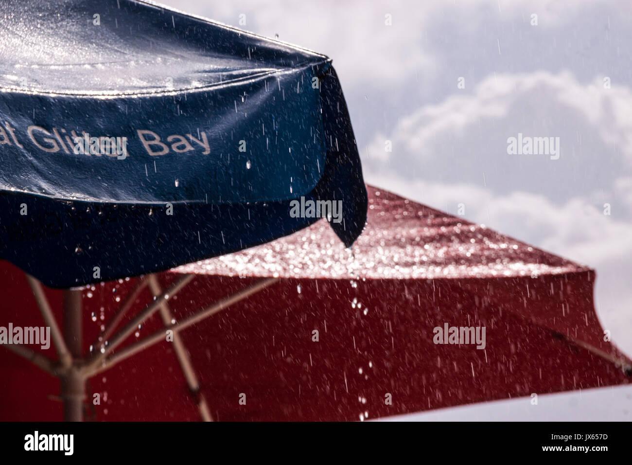 Regen Gießen von Sonnenschirmen in Barbados, Karibik Inseln Stockbild